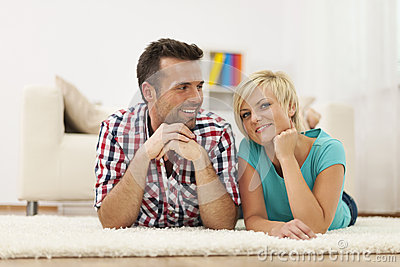 Smiling couple lying down on carpet