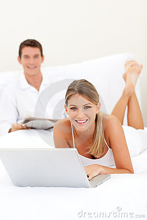 Smiling couple relaxing on their bed