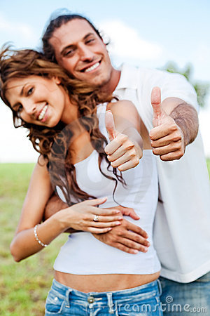 Smiling couple showing thumbs-up