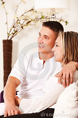 Smiling couple sitting on sofa