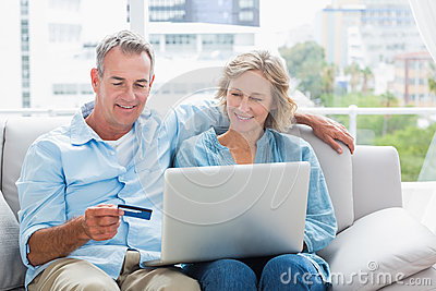 Smiling couple sitting on their couch using the laptop to buy on