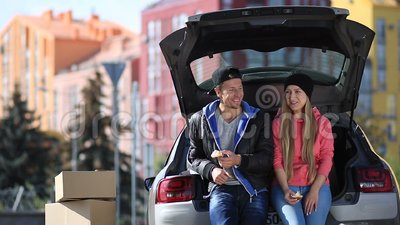 Smiling couple sitting in trunk of modern car stock footage