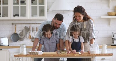 Smiling couple teaching children siblings flattening dough with rolling pins. Smiling couple teaching children siblings flattening dough with rolling pins stock video