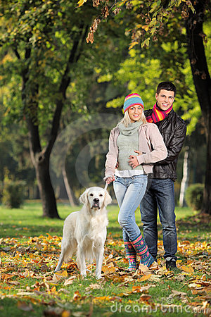 A smiling couple and their dog posing in the park