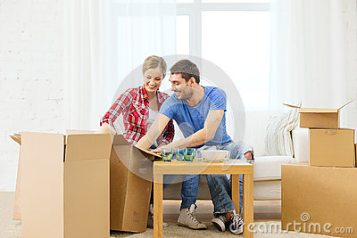 Smiling couple unpacking kitchenware
