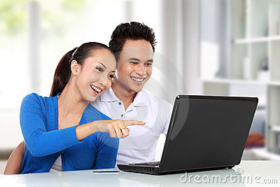 Smiling couple using a laptop