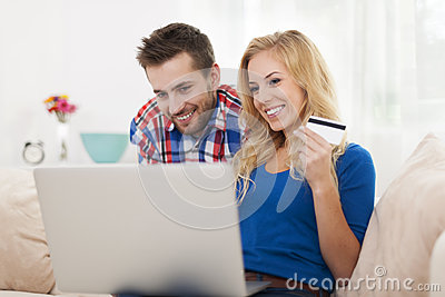 Smiling couple using laptop
