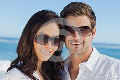 Smiling couple wearing sunglasses and looking at camera