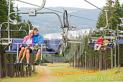 Smiling couples using chair lift scenic landscape