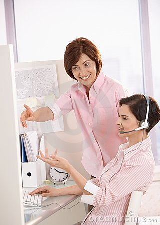 Smiling coworkers discussing work in office