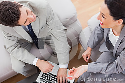 Smiling coworkers talking and using laptop sitting on sofa