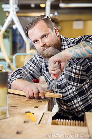 Free Smiling Craftsman Files Wooden Guitar Neck In Workshop Royalty Free Stock Photos - 66959288