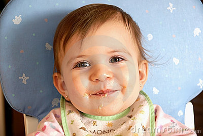 Smiling cute baby girl eating cereal