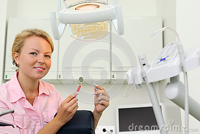 Smiling dentist sits in cabinet of dental clinic