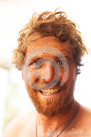 Smiling dirty ginger caveman with big beard and filth all over is face.
