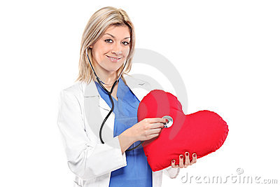 Smiling doctor examining a red heart shaped pillow