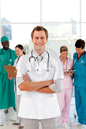 Smiling doctor with his team in the background