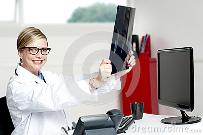 Smiling doctor looking at scanned x-ray report