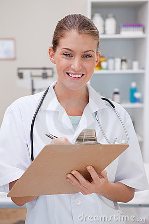Smiling doctor taking notes on clipboard