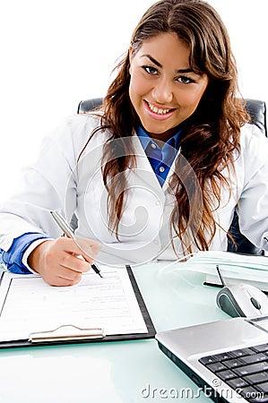 Smiling doctor writing prescription