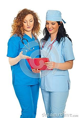 Smiling doctors women reading clipboard
