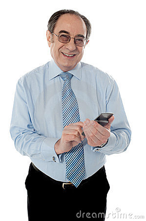 Smiling elder business executive texting