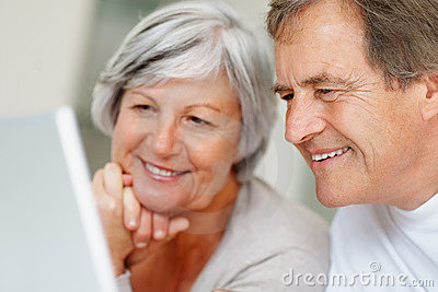 Smiling elderly couple using a laptop together