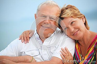 Smiling elderly couple on veranda near seacoast