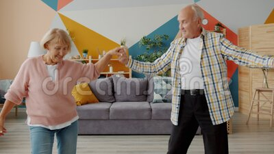 Smiling elderly lady and man dancing at home holding hands enjoying music indoors. Smiling elderly lady and man are dancing at home holding hands enjoying music stock video
