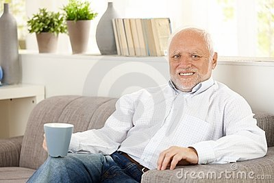 Smiling elderly man having coffee on sofa