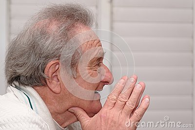 Smiling elderly man resting his head on hands