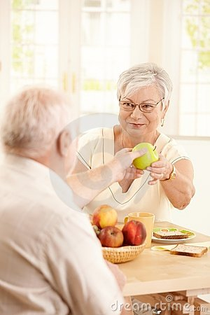 Free Smiling Elderly Wife Handing Apple To Husband Stock Images - 16987034