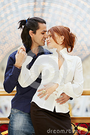 Smiling embracing couple stands leaned on banister