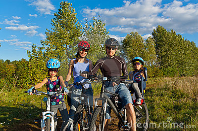 Smiling family cycling outdoors