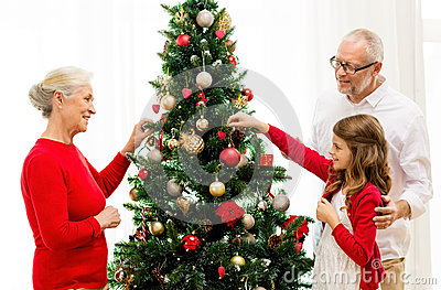 Smiling family decorating christmas tree at home