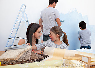Smiling family decorating their new home