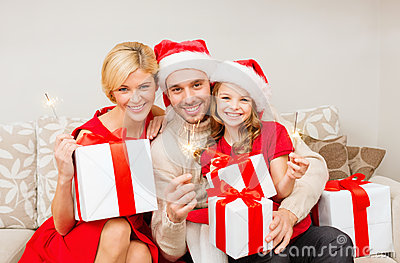 Smiling family holding gift boxes and sparkles