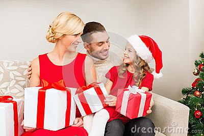 Smiling family holding many gift boxes