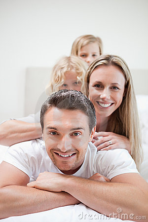Smiling family lying on bed