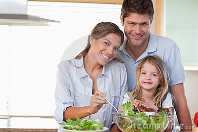 Smiling family preparing a salad