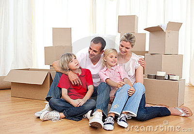 Smiling family relaxing while moving house