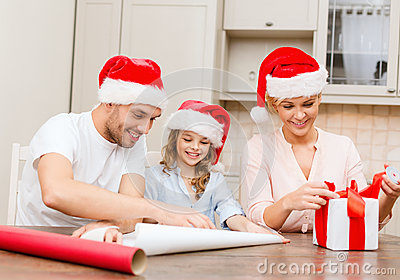 Smiling family in santa helper hats with gift box