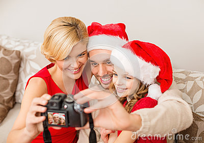 Smiling family in santa helper hats taking picture