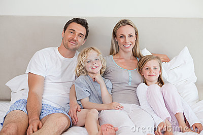 Smiling family sitting on the bed