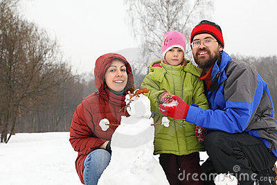 Smiling family and snowman