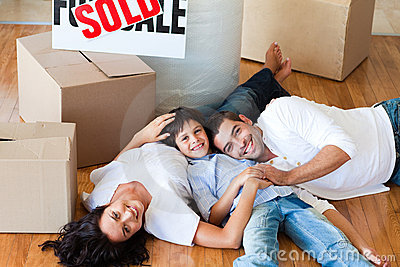 Smiling family in their new house lying on floor