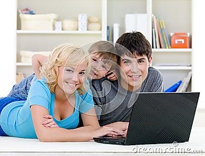 Smiling family using laptop