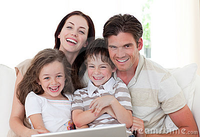 Smiling family using a laptop in the living-room