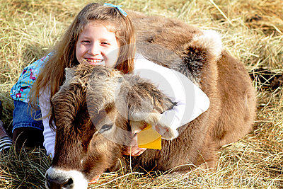 Smiling farm girl and pet calf