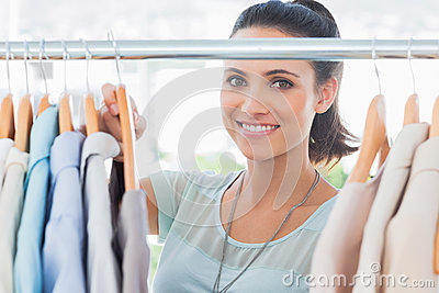 Smiling fashion designer looking at clothes